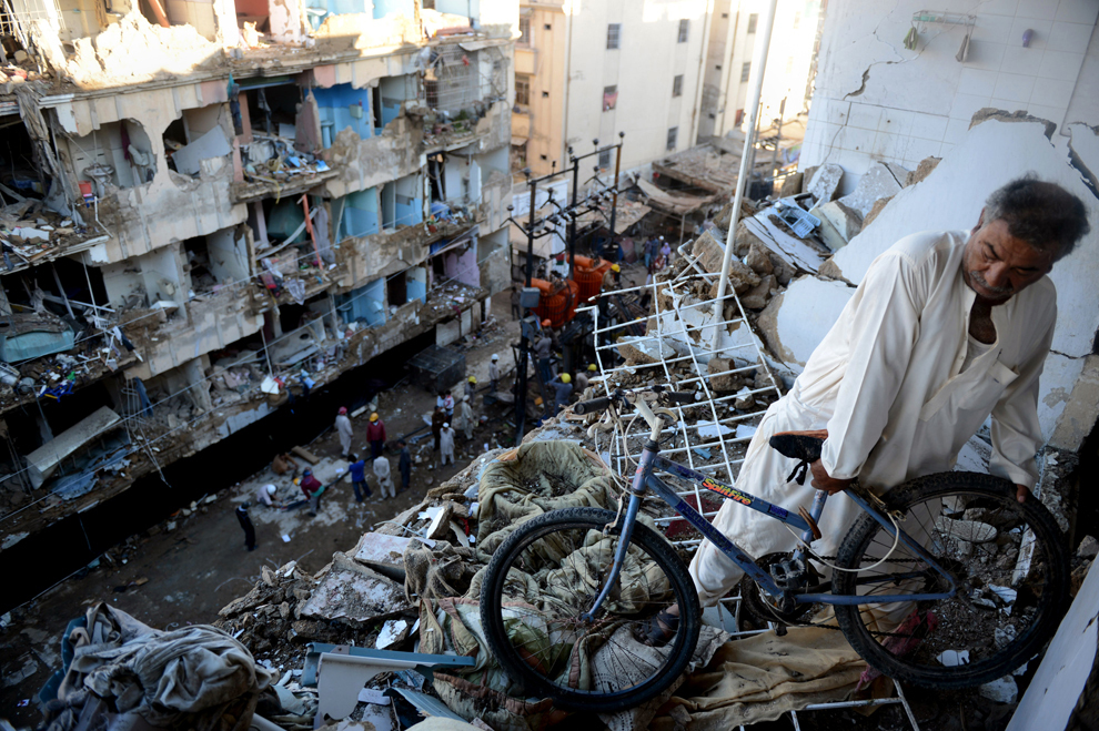 Un bărbat pakistanez îşi mută bicicleta din casa avariată de explozia unei bombe, în Karachi, luni, 4 martie 2013, a doua zi de la momentul atacului.