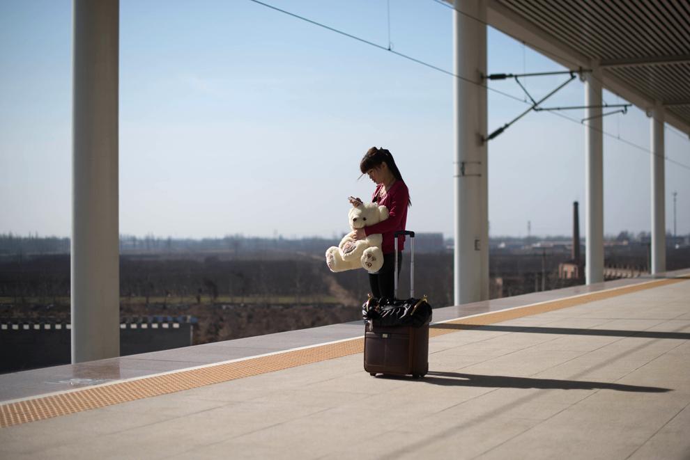 O femeie ţine în braţe un urs de pluş, în timp ce aşteaptă pe un peron din Xingtai, la sud de Beijing, în China, duminică, 10 martie 2013.