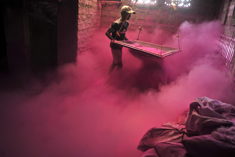 Un muncitor indian cerne pudră colorată (gulal), care va fi folosită în timpul festivalului Holi, la perifieria oraşului Siliguri, în India, miercuri, 20 martie 2013.