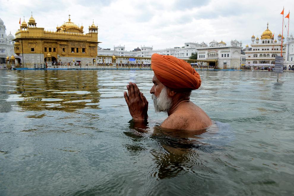 Un credincios sikh indian se îmbăiază în bazinul sacru cu ocazia sărbătorii 'Hola Mohalla', celebrată de obicei în martie, după sărbătoarea hindusă Holi, la Templul de Aur din Amritsar, joi, 28 martie 2013.
