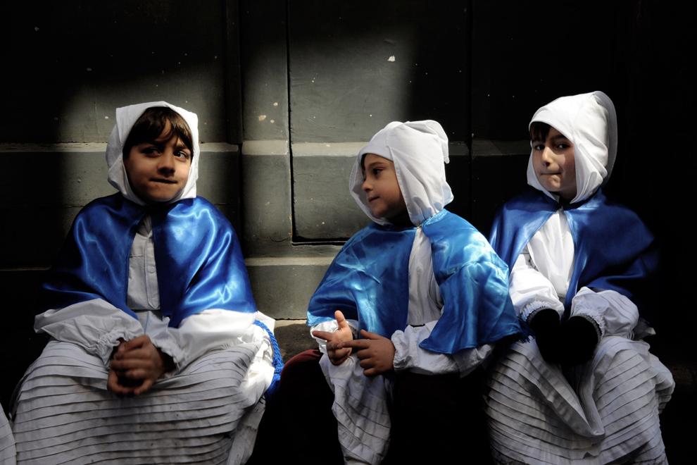 Tineri penitenţi se relaxează vineri, 29 martie 2013, în timpul procesiunii din Vinerea Mare, când care alegorice cu statui din hârtie ce reproduc scene biblice sunt purtate pe străzile insulei Procida din sudul golfului Napoli.