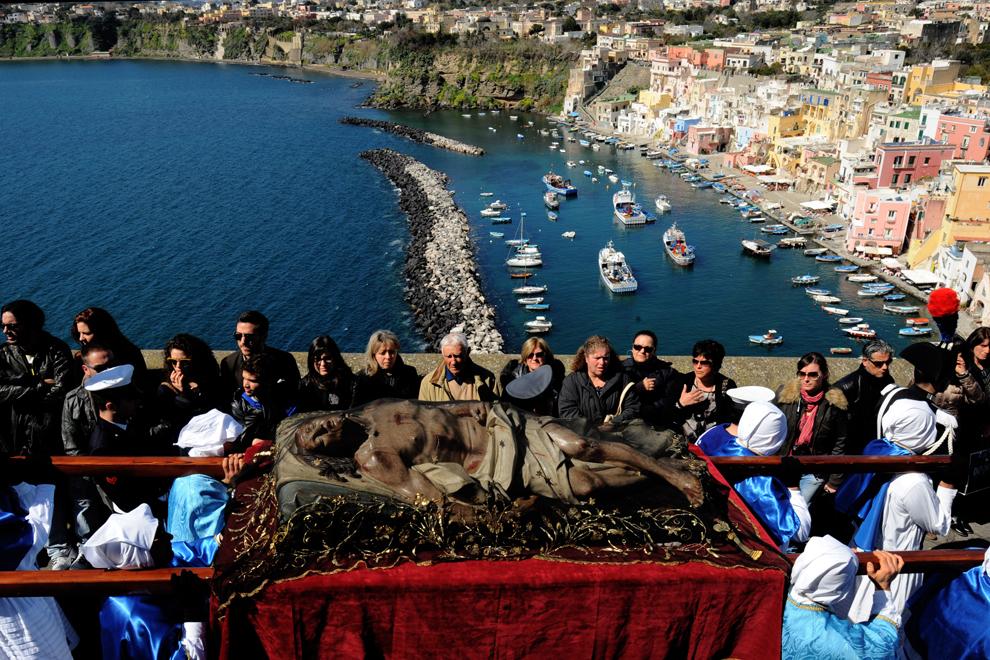 Mai mulţi penitenţi poartă pe umeri o sculptură a lui Iisus Christos, în timpul procesiunii din Vinerea Mare, pe insula Procida din sudul golfului Napoli, vineri, 29 martie 2013.