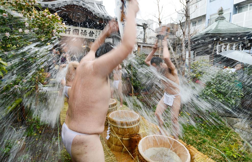 Asceţi budişti  îşi stropesc corpul cu apă rece la sfârşitul celor o sută de zile de post budist, în care s-au rugat pentru pacea în lume, la templul Nose Myokenzan Betsuin din Tokyo, vineri, 15 februarie 2013.