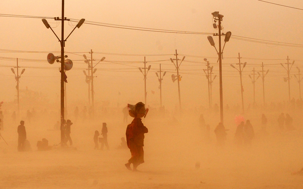 Credincioşi hinduşi merg în timpul unei furtuni de nisip, după ce au făcut baia sfântă la confluenţa fluviului Gange cu râul Yamuna şi miticul Saraswati, în timpul festivalului Maha Kumbh, în Allahabad, miercuri, 5 februarie 2013.