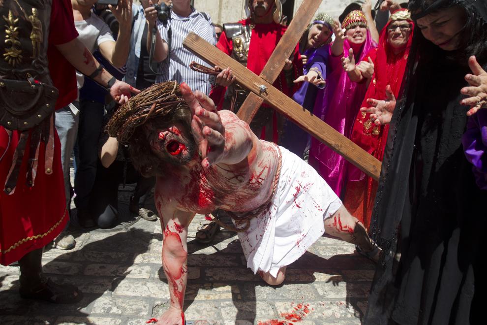 Un pelerin creştin reconstituie crucificarea lui Iisus Christos pe drumul către locul execuţiei, cunoscut ca 'Via Dolorosa' sau 'Calea Suferinţei', în Vinerea Mare, în Oraşul Vechi al Ierusalimului, vineri, 29 martie 2013.
