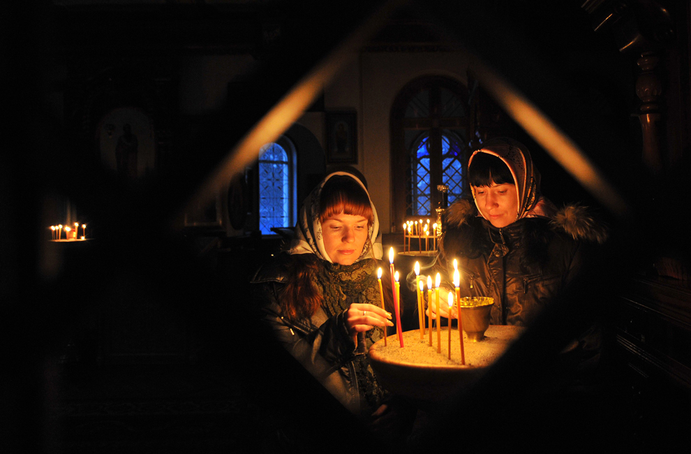 Două surori aprind lumânări în timpul slujbei religioase ţinute cu ocazia Crăciunului Ortodox pe stil vechi, într-o biserică din satul Sokuluk, aflat la 30 de km de Bishkek, în Kîrgîzstan, duminică, 6 ianuarie 2013.