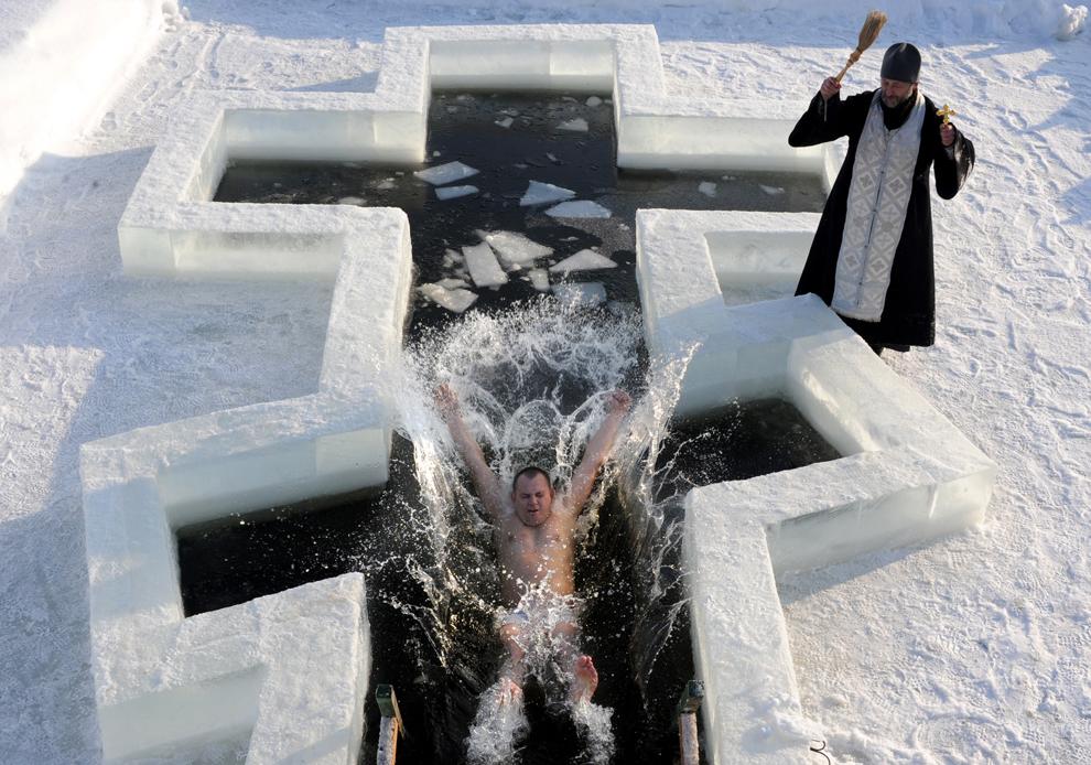 Un credincios ortodox sare în apele îngheţate, în timp ce un preot îl binecuvântează, în ajunul sărbătorii Bobotezei, în Pilnitsa, la 30 de km de Minsk, în Belarus, vineri, 18 ianuarie 2013.