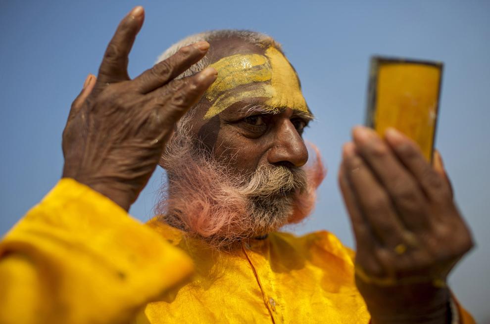 Un sadhu hindus, considerat a fi un om sfânt, îşi vopseşte fruntea, după s-a îmbăiat la confluenţa fluviului Gange cu râul Yamuna şi miticul Saraswati, în timpul festivalului Maha Kumbh, în Allahabad, marţi, 19 februarie 2013.
