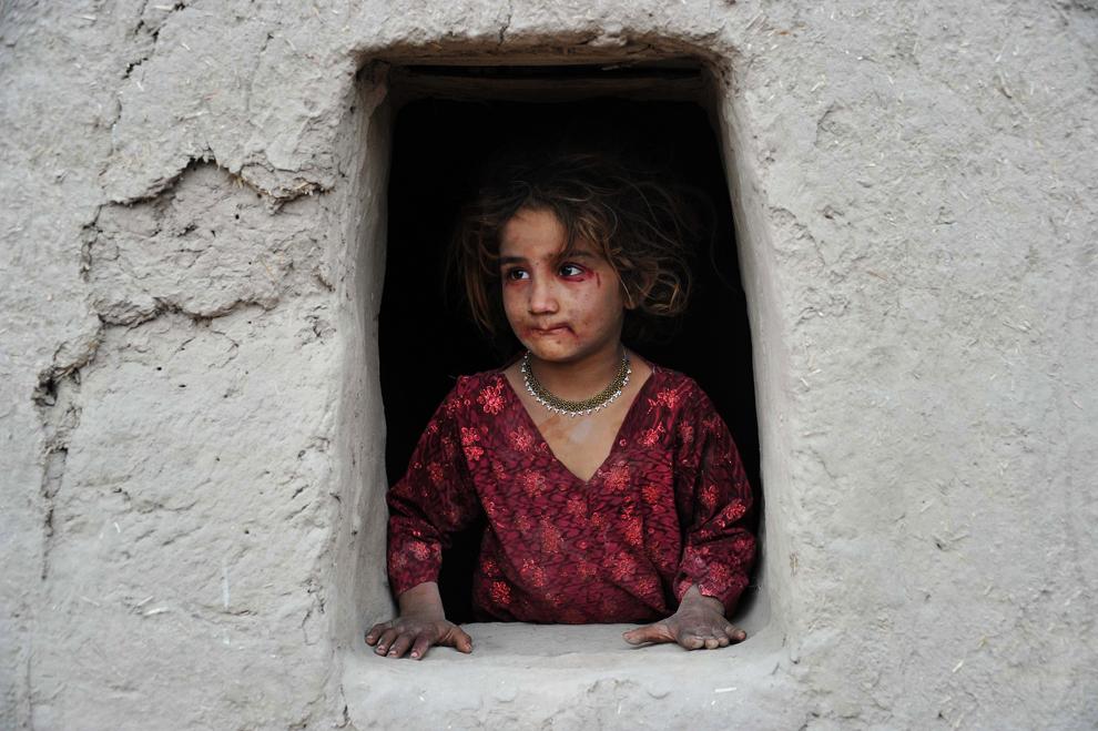 O fetiţă afgană priveşte pe fereastră, într-o locuinţă de la periferia Jalalabad, miercuri, 30 ianuarie 2013.
