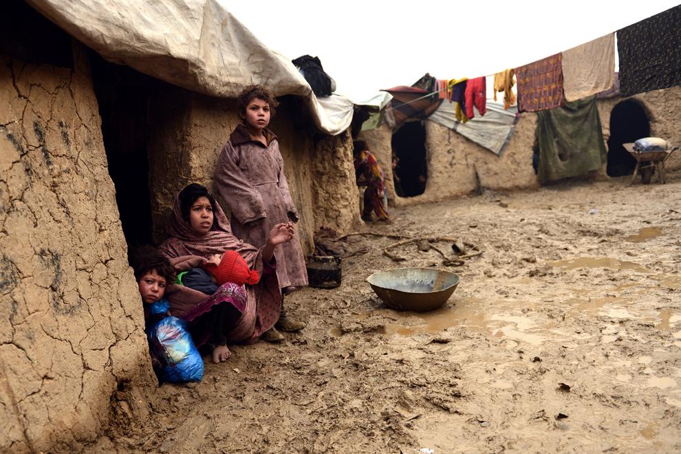 O familie evacuată priveşte către cameră, din uşa colibei, aflată în tabara Nassaji, est de Kabul, vineri, 1 februarie 2013.