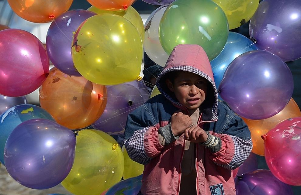 Un copil afgan ţine în mână baloane de vânzare, într-o zi friguroasă de iarna, în Kabul, joi, 7 februarie 2013.