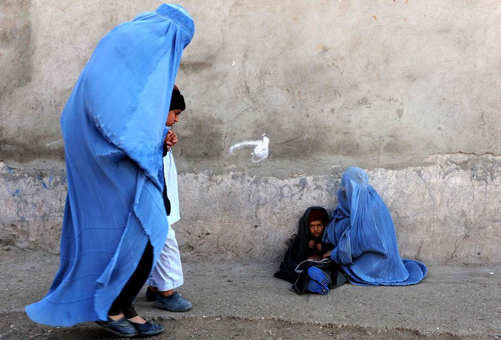 O femeie afgană, îmbrăcată în burqa, cerşeşte ţinând în braţe un copil, în timp ce alte femei trec pe lânga ei, pe o stradă din Herat, duminică, 10 februarie 2013.