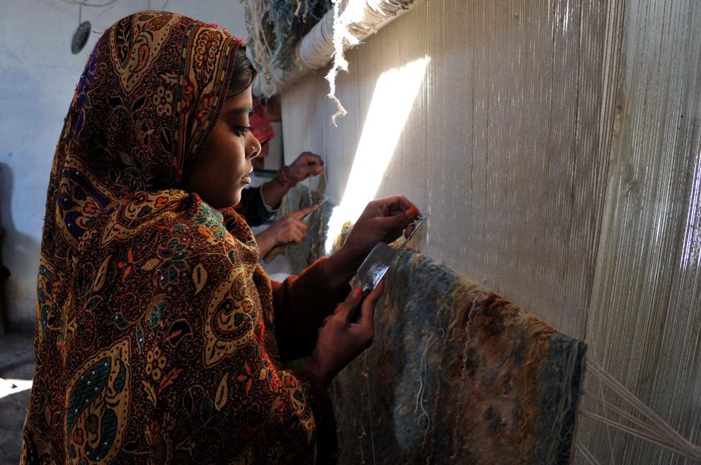 O fetiţă afgană ţese un covor, într-o fabrică tradiţională de covoare, în Jalalabad, capitala provinciei estice Nangarhar, vineri, 1 martie 2013.