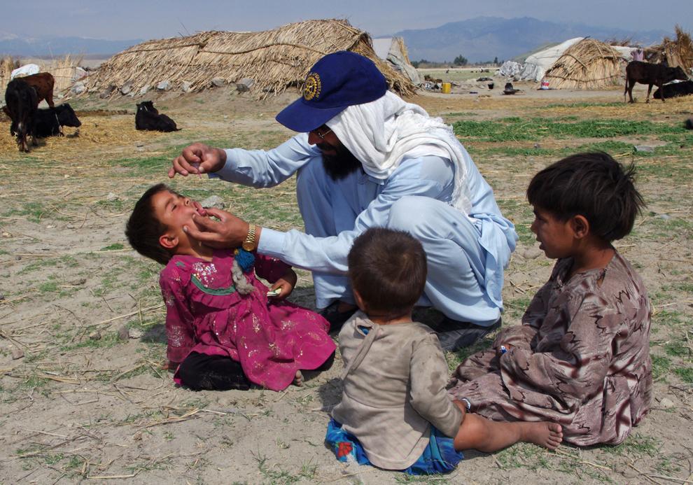 Un afgan administrează unui copil nomad picături cu vaccinul anti-poliomielită, în cea de-a doua zi a campaniei de vaccinări, la periferia Mihtarlam, luni, 11, martie 2013.
