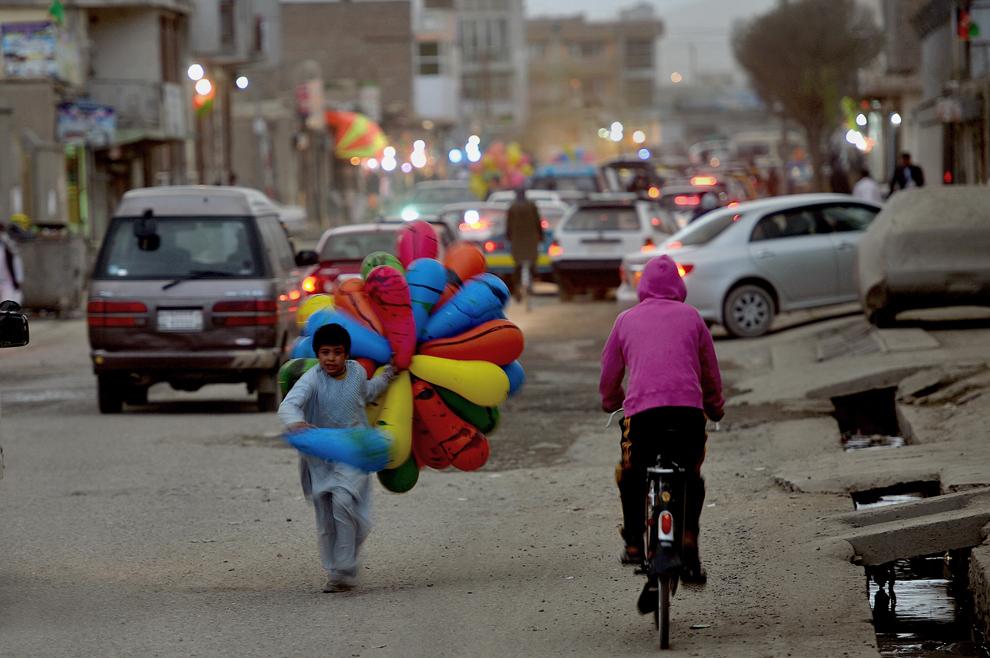 """Un copil afgan ce vinde baloane, aleargă către un client pe o stradă din Kabul, marţi, 2 aprilie 2013. Conform unui raport UN, 36% din populaţia Afganistanului, aproximativ nouă milioane de afgani trăiesc în """"sărăcie absolută""""."""