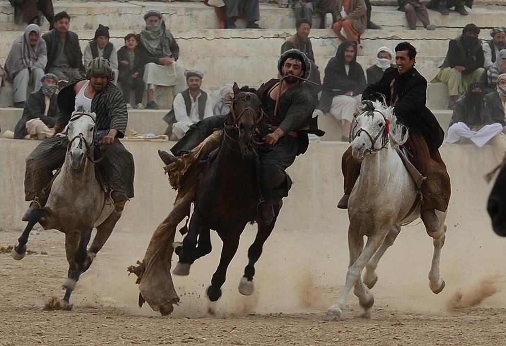 """Călăreţi afgani concurează pentru o carcasă de viţel, în timpul unui joc de """"buzkashi"""", cu ocazia Nowruz (principala sărbătoare în care se celebreaza anul nou în Afganistan), în nordul Mazar-i Sharig, joi, 21 martie 2013."""