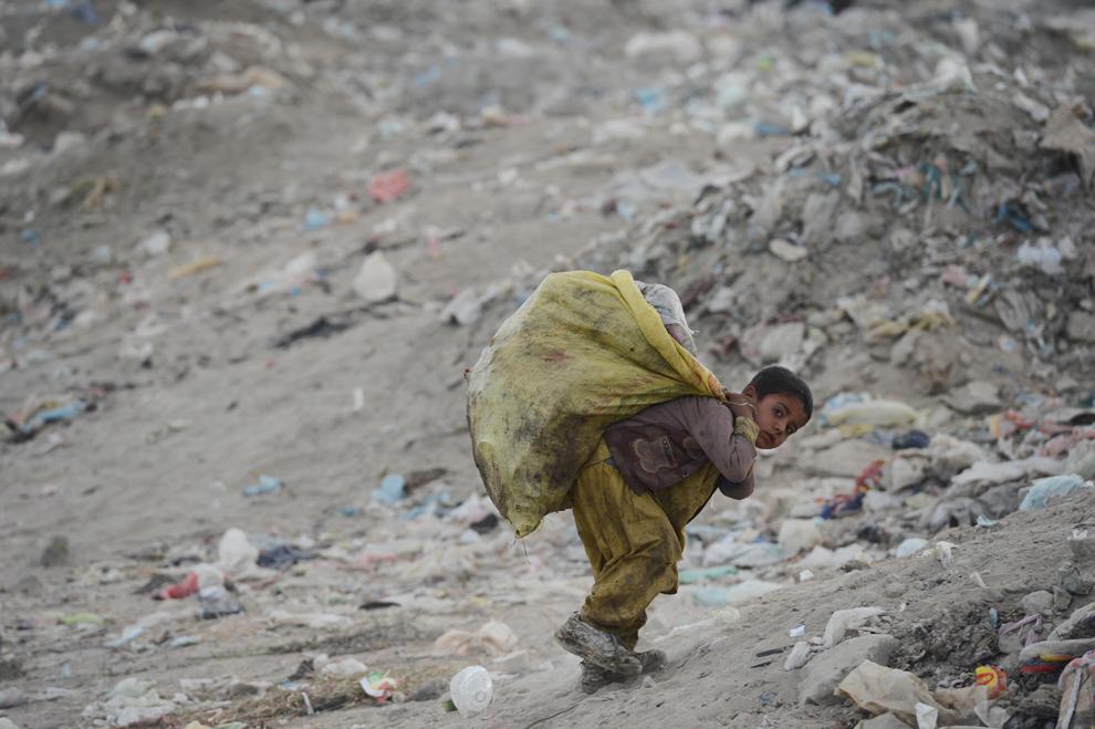 Un copil ce colectează gunoi, cară materiale reciclabile la o groapă de gunoi de la periferia Kabul-ului, miercuri, 17 octombrie 2012.