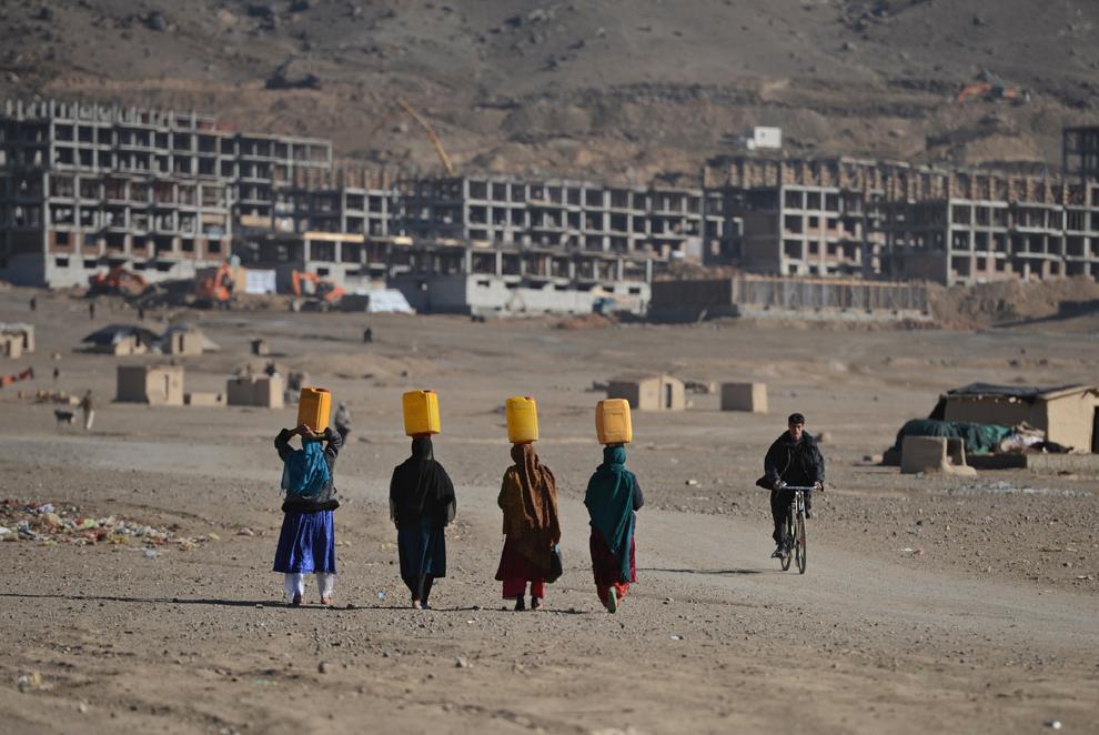 Femei nomade (Kuchis) transportă canistre cu apă pe cap, la periferia Kabul, vineri, 30 noiembrie 2012.