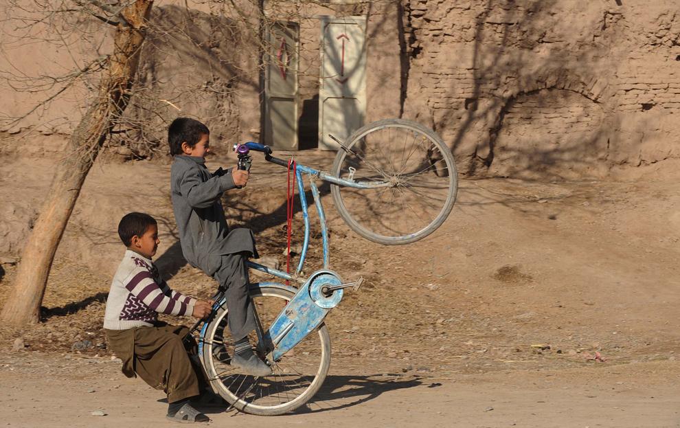 Copii afgani se joacă cu o bicicletă, pe o stradă din Herat, luni, 14 ianuarie 2013.