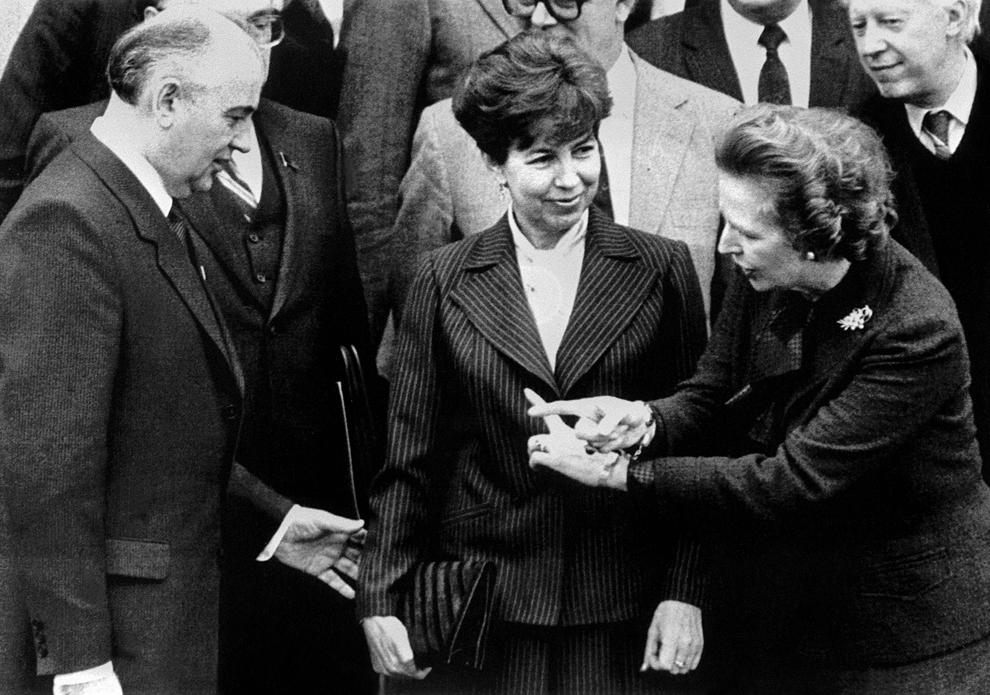 Margaret Thatcher le indică unde să stea, pentru a fi fotografiaţi, membrului biroului politic sovietic, Mihail Gorbaciov, şi soţiei sale, Raisa, în timpul întâlnirii acestora de la reşedinţa Chequers a premierului britanic, duminică, 16 decembrie 1984.