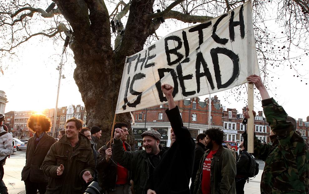 Mai multe persoane afişează un mesaj ofensator în timp ce se bucură la aflarea veştii morţii fostului premier britanic Margaret Thatcher, în Londra, luni, 8 aprilie 2013.