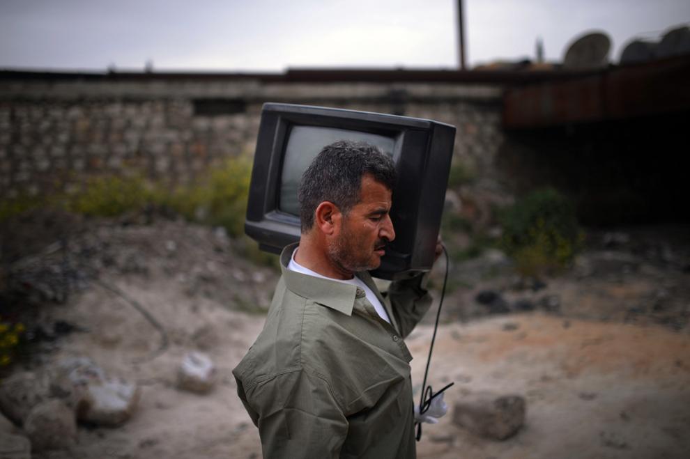Un bărbat ţine un televizor pe umăr la ieşirea din cartierul Sheikh Maqsud, în Alepp, Siria, joi, 4 aprilie 2013.