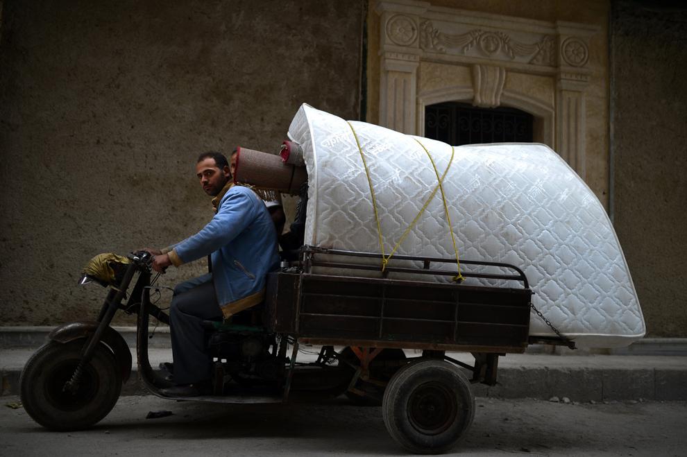 Un bărbat ce transportă  bunuri iese din cartierul Sheikh Maqsud, în Alepp, Siria, joi, 11 aprilie 2013.