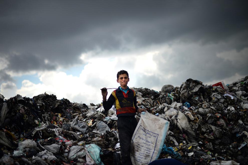 Un băieţel sirian ţine în mână un sac, în timp ce colectează obiecte din plastic şi metal de la o groapă de gunoi din Alepp, Siria, miercuri, 17 aprilie 2013.
