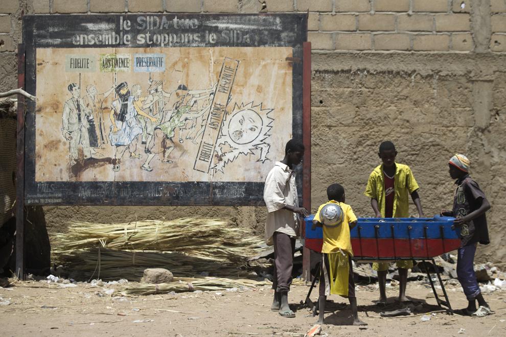 Tineri se joacă lângă un poster din campania împotriva SIDA, în Gao, Mali, joi, 4 aprilie 2013.