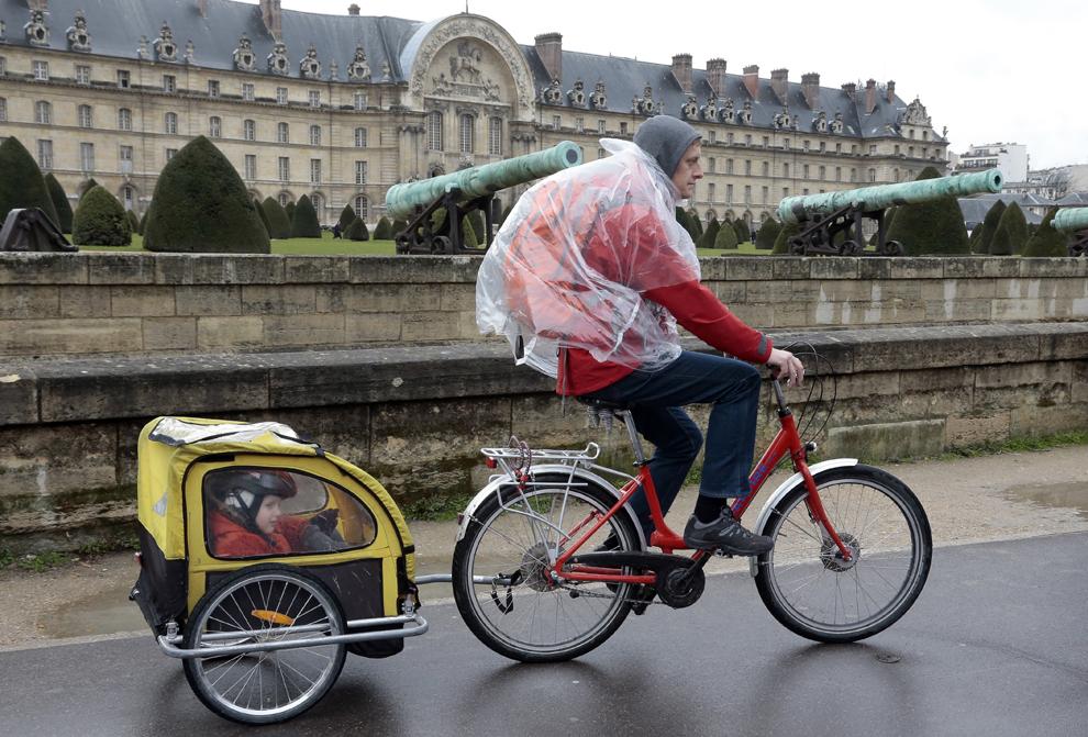 Un ciclist pedalează cu o remorcă ataşată în care se află copiii săi, în Paris, marţi, 9 aprilie 2013.
