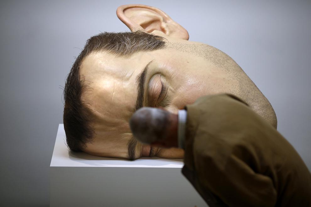"""Un bărbat priveşte către sculptura """"Mask II""""  a artistului australian Ron Mueck, în Paris, luni, 15 aprilie 2013."""