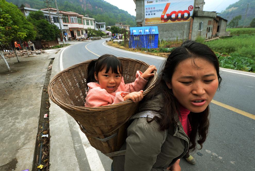 O femeie ce îşi ţine fetiţa într-un coş, merge către centrul de distribuire a mâncării, în Longmen, după ce un cutremur de 7 grade a lovit Lushan, provincia Sichuan, China, luni, 22 aprilie 2013.