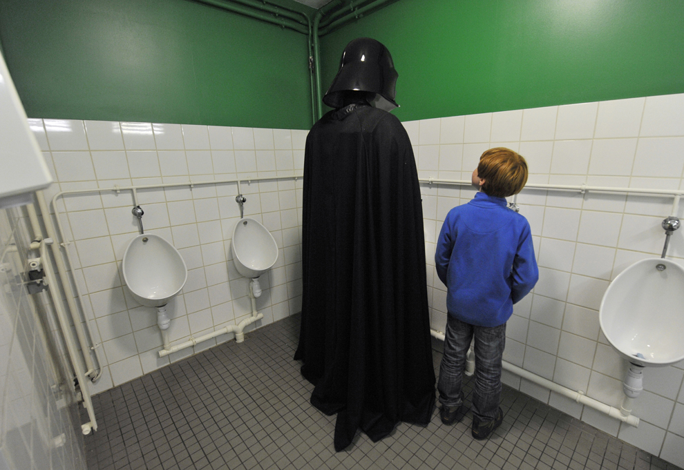 Un fan îmbrăcat ca Darth Vader stă într-o toaletă publică, în timpul unei convenţii Star Wars, în Cusset, Franţa, sâmbătă, 27 aprilie 2013.