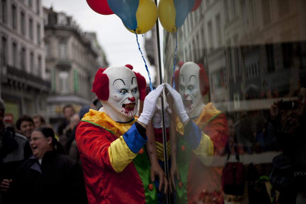 Un bărbat costumat în clown ia parte la Parada Zombie, pe străzile oraşului Bruxelles, sâmbătă, 6 aprilie 2013.