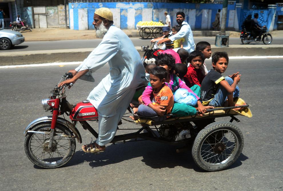 Copii pakistanezi  se plimbă cu o motocicletă cu trei roţi pe o stradă din Karachi,  vineri, 5 aprilie 2013.