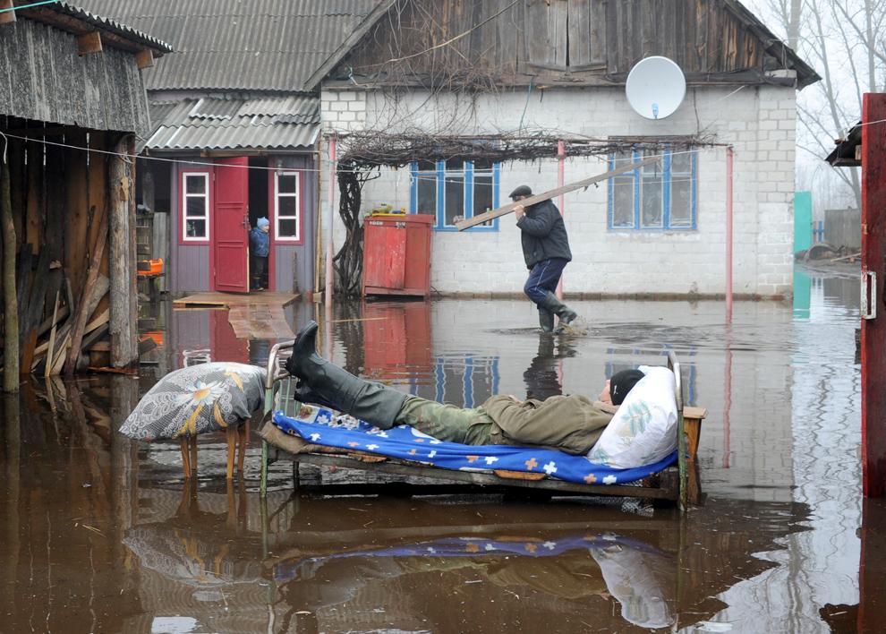 Un bărbat se odihneşte în aer liber, în timpul unei inundaţii de primăvară, în Khvoensk, Belarus, duminică, 14 aprilie 2013.