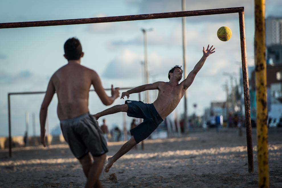 Tineri joacă fotbal pe plajă, în Recife, Pernambuca, Brazilia, duminică, 14 aprilie 2013.