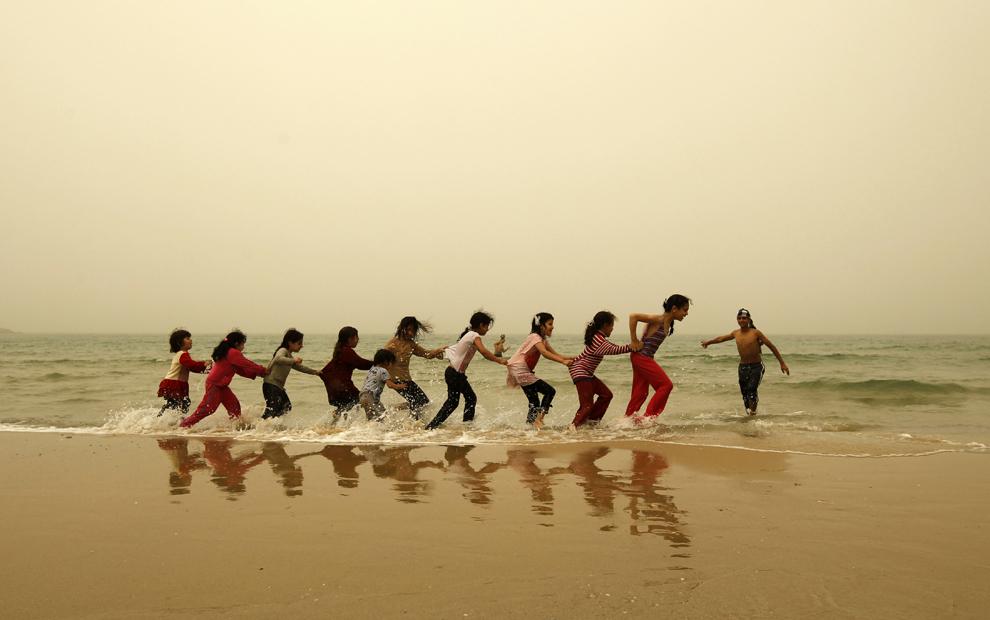 Copii palestinieni se joacă pe o plajă din Gaza în timpul unei furtuni de nisip, luni, 1 aprilie 2013.