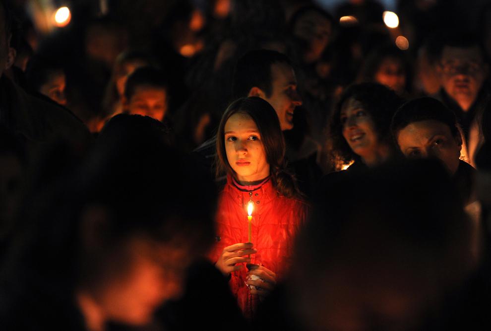 O tânără macedoneană ţine în mâini o lumânare în timpul slujbei religioase de Paşte de la miezul nopţii, în biserica Sfântul Dimitrie din Skopje, duminică, 15 aprilie 2012.