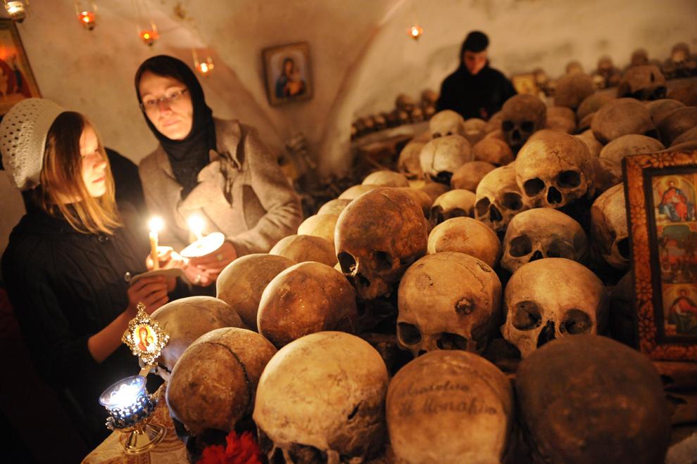 Credincioşi ortodocşi vizitează osuarul de la mănăstirea Pasărea la scurt timp după slujba religioasă de Paşte, în timp ce călugăriţele aprind lumânări pentru cei decedaţi, în satul Pasărea, la 20 de km de Bucureşti, duminică, 24 aprilie 2011.