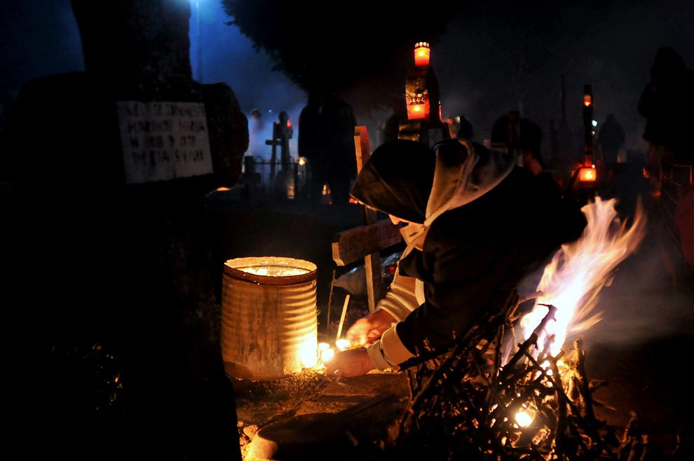 Localnici din satul Herăşti, judeţul Giurgiu, aprind focuri la mormintele celor dragi, cu ocazia sărbătorii de Florii, sâmbătă, 16 aprilie 2011. În noaptea de Florii, rudele celor decedaţi vin la cimitir şi împart mâncare şi băutură în memoria celor morţi.