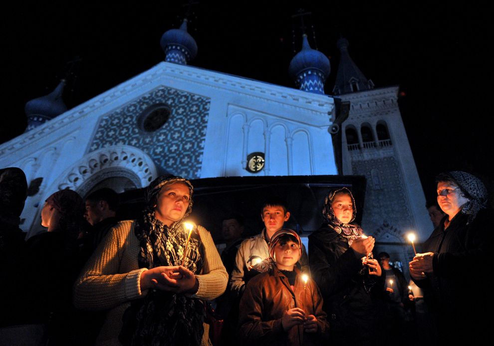 Credincioşi ortodocşi aprind lumânări pentru a sărbători Paştele, în timpul Slujbei de Înviere, în curtea unei biserici din Bishkek, în Kîrgîzstan, sâmbătă, 23 aprilie 2011.