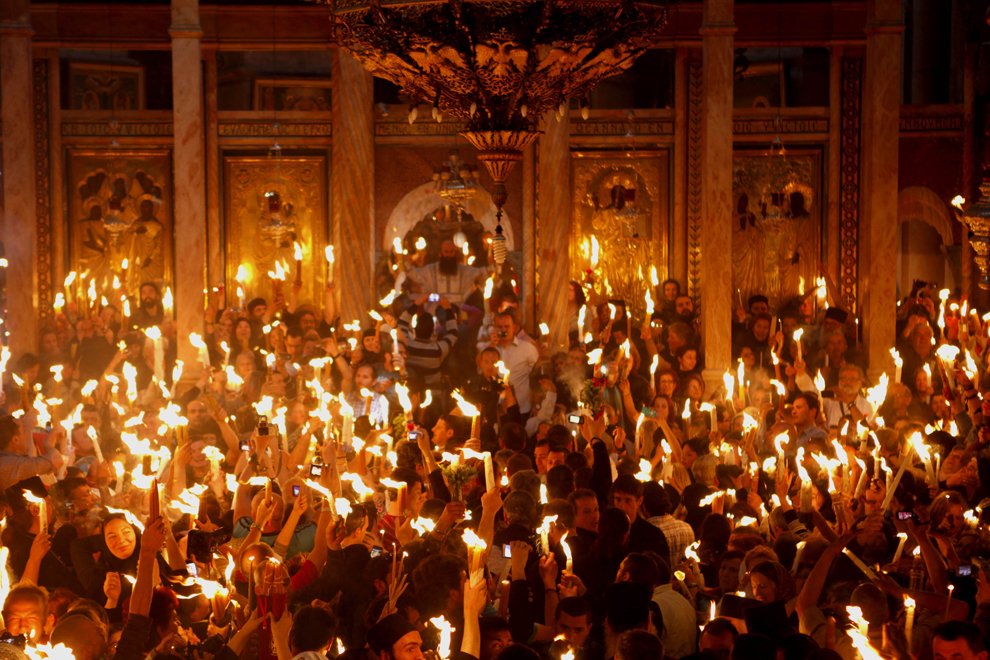 Credincioşi creştini ortodocşi ţin lumânări aprinse de la 'Focul Sfânt', în timp ce mii de pelerini s-au adunat în Biserica Sfântului Mormânt pentru a participa la ceremonia 'Luminii Sfinte', în oraşul vechi din Ierusalim, sâmbătă, 14 aprilie 2012.
