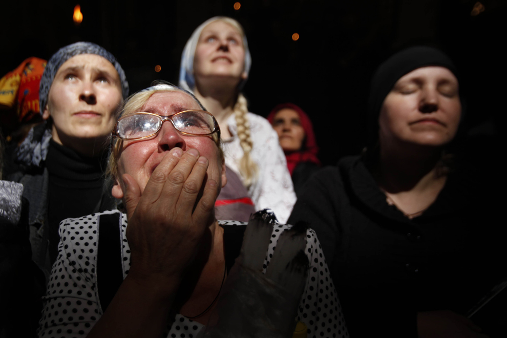Credincioşi creştini ortodocşi îşi ţin capetele ridicate în timp ce o rază de lumină pătrunde printr-o fereastră în Biserica Sfântului Mormânt, în timpul ceremoniei 'Focului Sfânt' din ajunul Paştelui ortodox, sâmbătă, 14 aprilie 2012.