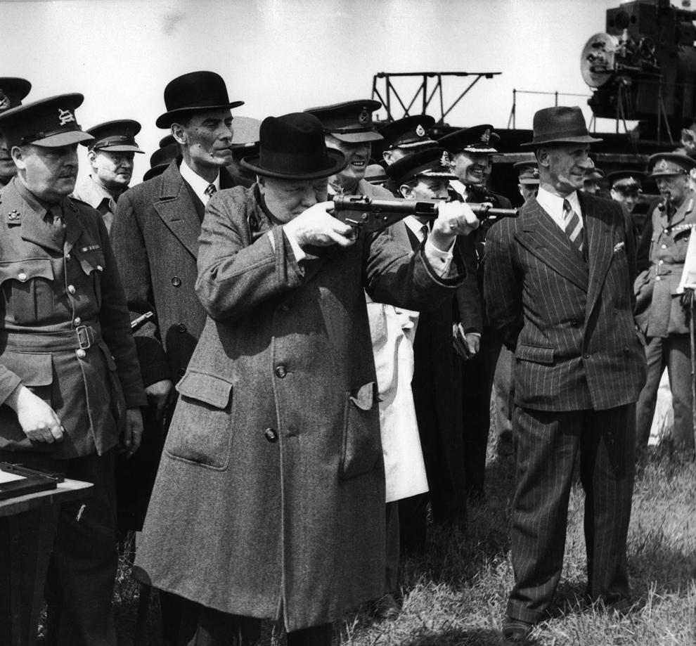"""Prim ministrul britanic, Sir Winston Churchill (C), înconjurat de ofiţeri ai armatei britanice testează una din noile mitraliere """"Sten"""", la începutul anului 1941, în regiunea Kent."""