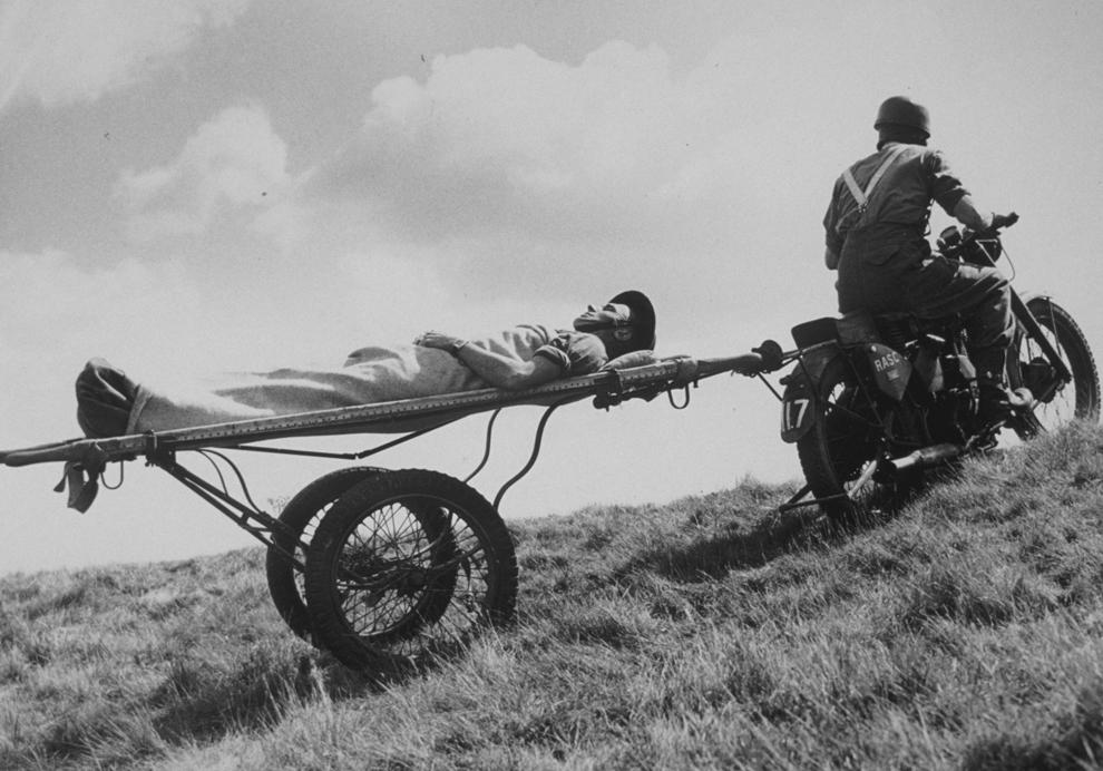 Un motociclist al RAMC (Royal Army Medical Corps) transportă un rănit către punctul de prim ajutor, în 1943, în timpul celui de-al doilea război mondial.