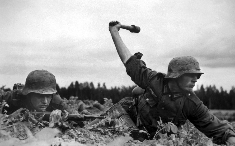 """Undeva pe frontul rusesc, un soldat german se ridicǎ pentru a arunca o grenada model 24, cunoscută popular ca o """"grenadă băţ"""" sau o """"maşină de tocat cartofi"""", în timp ce tovarăşul său urmăreşte inamicului, în 1941."""