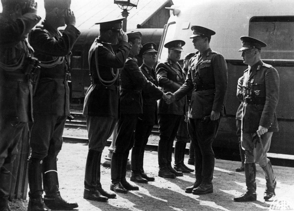 Prim-ministrul român Ion Antonescu şi Regele Mihai I al României dau mâna cu ofiţeri ai Statului Major General, la sosirea în gara Cernăuţi, în iulie 1941.