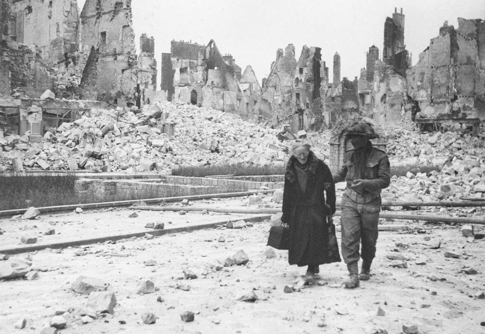 Fotografie făcută în iunie 1944 ce arată un soldat american care ajută o femeie în vârstă, în oraşul Caen, Franţa, complet distrus de bombardamentele de la sfârşitul celui de-al doilea război mondial.