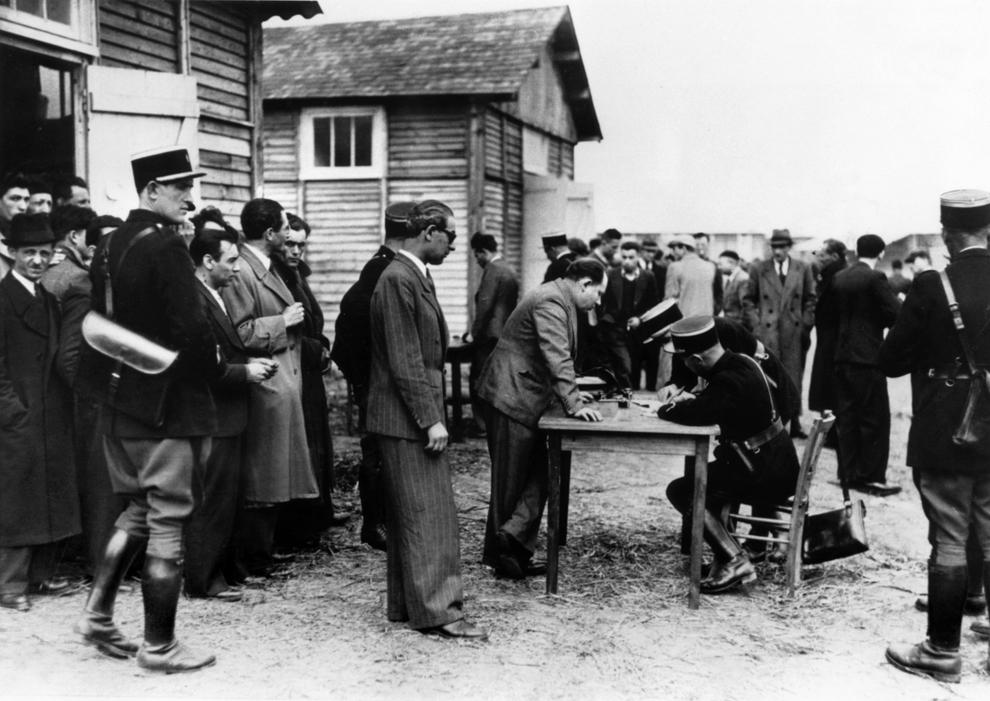 Fotografie datată mai 1941 ce înfăţişează mai mulţi evrei, în special de naţionalitate poloneză, în timp ce sunt înregistraţi de poliţişti francezi, dupa sosirea acestora în lagărul de tranzit de la Pithiviers.